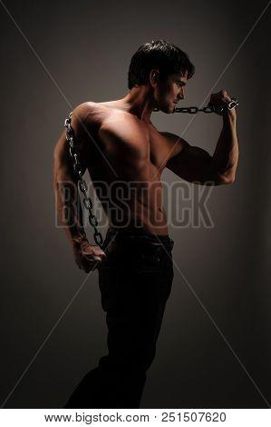 The sexy man holds a chain and flexes his nice muscles. stock photo