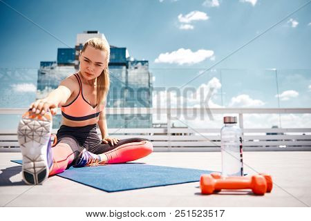 Focus on fit young woman improving flexibility after work out with equipment. She is straightening one leg while bending body to it and catching sneaker with hand. Pair of dumbbells and bottle with water are standing near mat on sunny terrace in height stock photo
