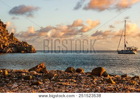 Travel photo in St. Barths, Caribbean. Sailing boat with a beautiful and pink sky in background in St. Barths . stock photo