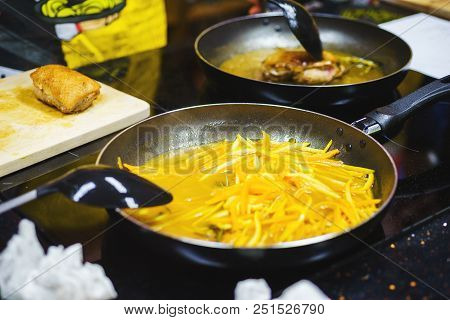 Orange peel for cooking sauce and roasting turkey breast. A close-up of grated orange peel in a frying pan. Stages of cooking the breast with oranges. Soft focus. stock photo