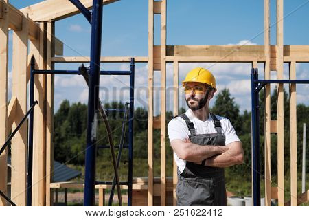 Portrait of a male builder in overalls and a yellow helmet on the roof of a frame house. stock photo