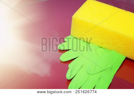 Yellow sponge and green gloves laying on car bonnet. Wash waxing or care concept. Place for text stock photo