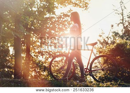 Young cute romantic girl walking with bicycle on the sunset in green summer park stock photo