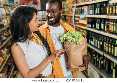 young african american couple with smartphone and paper bag with food in supermarket stock photo