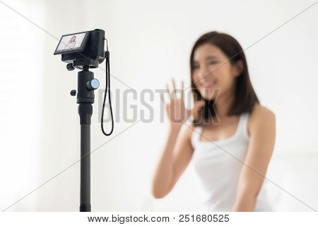 Young Asian female blogger waving hand and recording video in white room at home. stock photo