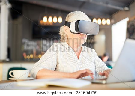 Mature grey-haired woman typing on laptop keypad while watching webcast in vr headset stock photo