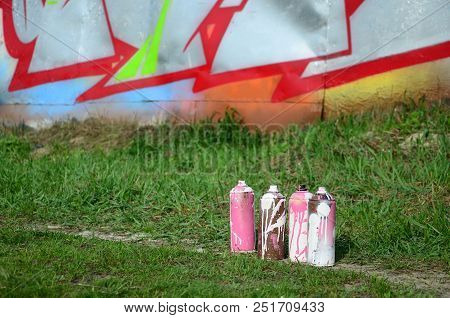 A few used paint cans lie on the ground near the wall with a beautiful graffiti painting. Street art and vandalism concept. stock photo