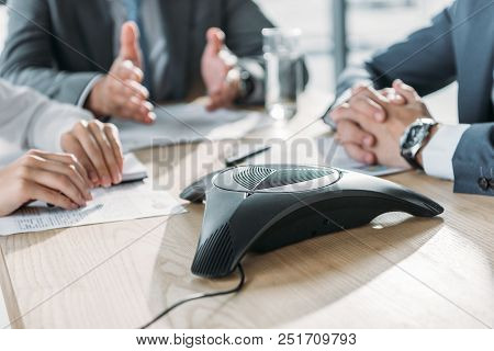 cropped shot of business people having conversation and using speakerphone at modern office stock photo