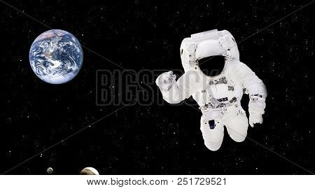 Spaceman close up in outer space. Astronaut in spacesuit close up isolated on black background. Planet Earth from outer space. Elements of this image furnished by NASA stock photo