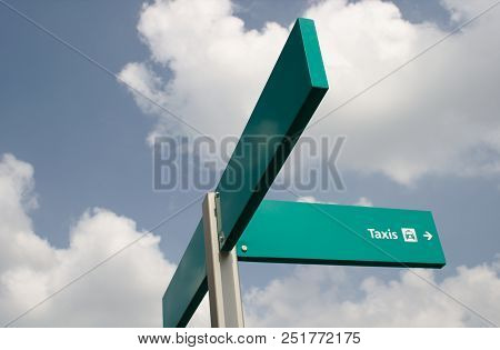 A green taxi signpost taken against a blue sky with clouds. Space to the left for text. stock photo