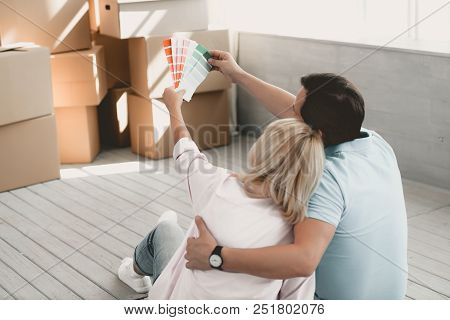 Man and Woman Sitting on Floor After Moving to New House Look at Palette of Paints Choosing Right One for Painting Floor. New Home. Moving House Day and Real Estate Concept. New Apartment Concept. stock photo