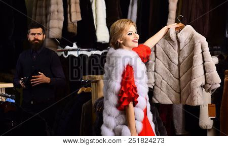 Girl with smiling face wearing white mink fur. Expensive shopping concept. Couple in love shopping in fur mall. Woman in white fur coat with worried bearded macho behind her looking for new overcoat. stock photo