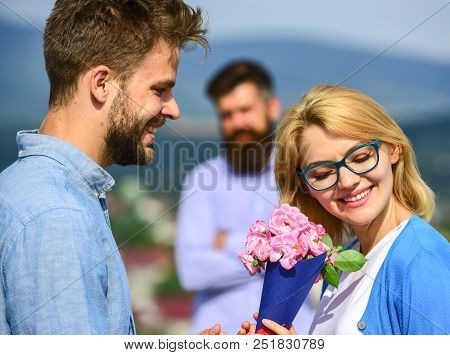 Couple in love dating while jealous husband fixedly watching on background. Lovers meeting outdoor flirt romance relations. Unrequited love concept. Couple romantic date lover present bouquet flowers. stock photo