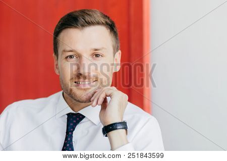 Prosperous young male entrepreneur dressed in white shirt, looks positively at camera, being confident in his success, isolated over red and white background, thinks about starting new career stock photo