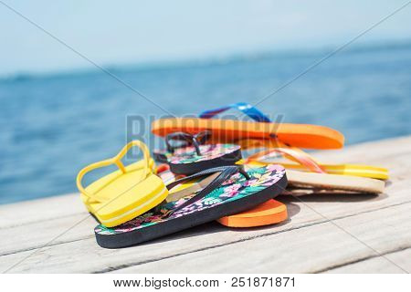 closeup of a pile of some different pairs of colorful flip-flops on a wooden pier next to the water stock photo