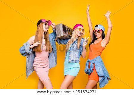 Stereo fan audio cassette tape hip-hop old school portable culture concept. Portrait of active trio gesturing peace symbol enjoying rest relax singing isolated on vivid yellow background stock photo