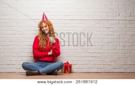 Young redhead woman sitting over brick wall wearing birthday hat happy with big smile doing ok sign, thumb up with fingers, excellent sign stock photo