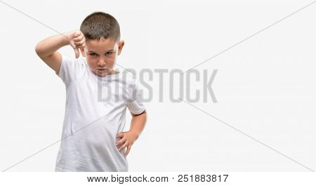 Dark haired little child with angry face, negative sign showing dislike with thumbs down, rejection concept stock photo