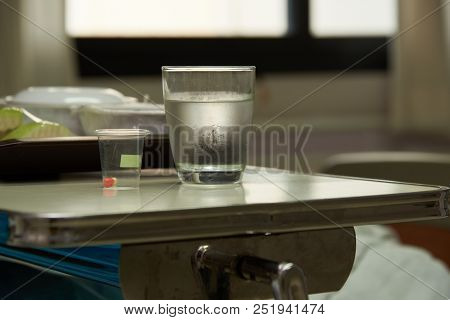 A capsule of medication and a glass of cold water for patient admitted in hospital. Meal in plates for patient stock photo