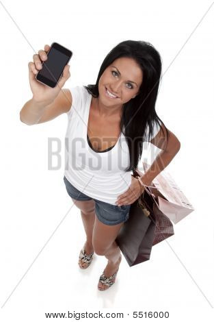 Diminishing perspective view of pretty young brunette woman holding smart phone. White background. stock photo