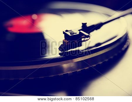 Close up view of old fashioned turntable playing a track from black vinyl toned with a retro vintage instagram filter effect app or action  stock photo
