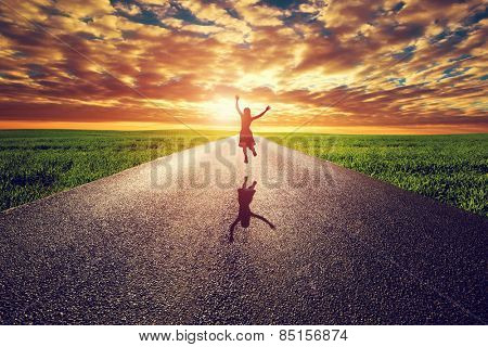 Happy woman jumping on long straight road, way towards sunset sun. Travel, happiness, win, healthy l