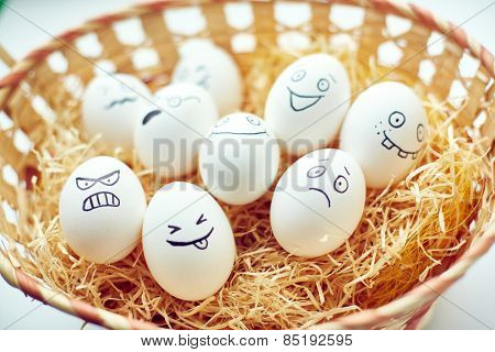 Basket with funny eggs with painted faces expressing different emotions
