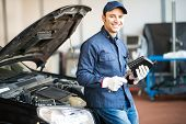 Portrait of an auto repairman holding a container of engine oil