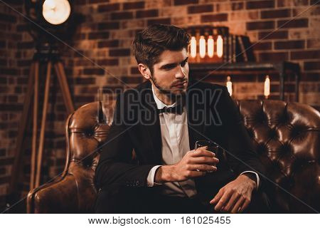 Successful young businessman in black suit with perfect hairstyle drinking cognac stock photo