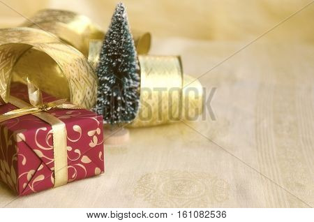 Christmas decoration: red gift box gold ribbon and mini fir tree on golden background. Winter holiday. Christmas or New Year concept. Copy space