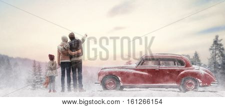 Toward adventure! Happy family relaxing and enjoying road trip. Mom, dad, child and vintage car on snowy winter nature background. Christmas holidays time. stock photo