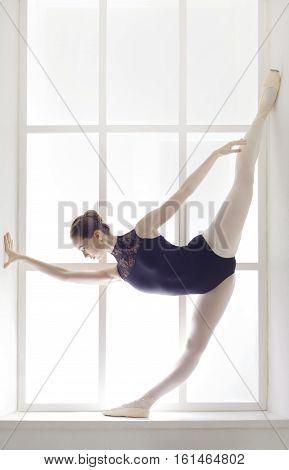 Classical Ballet dancer portrait. Beautiful graceful ballerine in black practice standing split ballet position at window background. Ballet class training, high-key. Vertical image