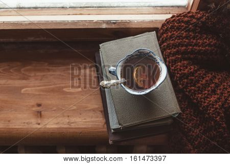 Warm and comfy autumn or winter concept. Book, cup of lemon tea and sweater on wooden window sill in old house. Reading and relaxing in cold fall weather at home. Quiet silent homely scene. stock photo