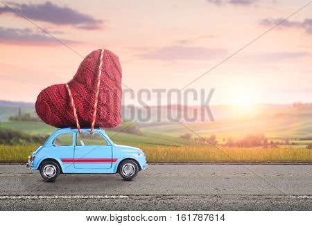 Blue retro toy car delivering heart for Valentine's day against blurred rural Tuscany sunset landsca