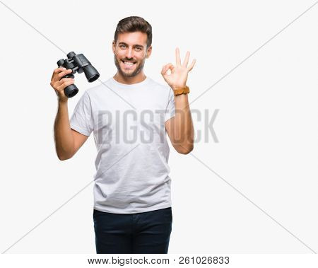 Young handsome man looking through binoculars over isolated background doing ok sign with fingers, excellent symbol stock photo