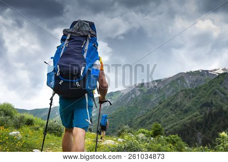 Tourist With Backpack Hike On Mountain Trek. Hiking In Svaneti, Georgia. Trekking In Mountains. Two