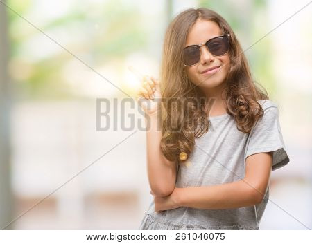 Brunette hispanic girl wearing sunglasses with a big smile on face, pointing with hand and finger to the side looking at the camera. stock photo
