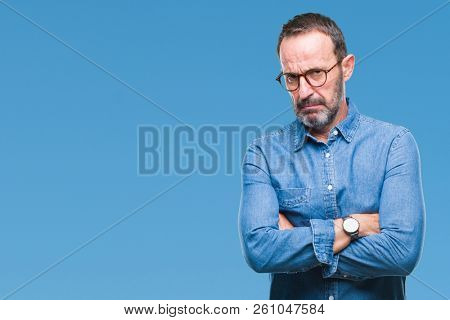 Middle age hoary senior man wearing glasses over isolated background skeptic and nervous, disapproving expression on face with crossed arms. Negative person. stock photo
