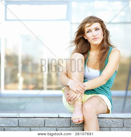 Cute student teenage girl sitting at urban scene. She is dreaming about something. stock photo