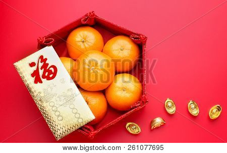 Group of orange tangerine in Chinese pattern tray and envelope packet ang pow with gold ingots on red table top. Chinese new year concep.Chinese Language on envelop is happiness,on ingot is wealthy stock photo