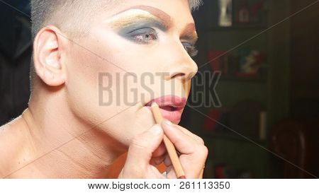 concept of travesty make-up. a handsome young man applies makeup on his face, sitting in front of a mirror in the dressing room. professional travesty artist. close-up, stock photo