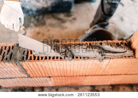 Close up hands of industrial bricklayer installing bricks on construction site stock photo