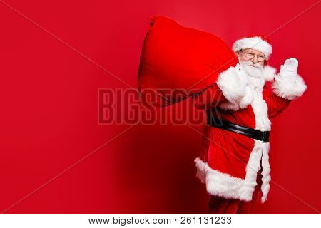 Cheerful nice peaceful Santa in eyeglasses wishes you merry Christmas waving hi hello holding keeping delivering huge sack with toys isolated over bright vivid red background stock photo
