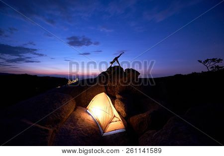 Brightly lit tourist tent on huge boulders and small silhouette of woman doing complicated gymnastic yoga exercises on mountain top against dramatic dark blue red sky at sunset. Adho Mukha Shvanasana stock photo