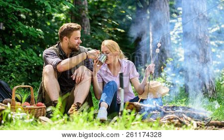 Food for hike and camping. Couple sit near bonfire eat snacks and drink. Couple in love camping forest hike. Hike snacks and beverages. Hike picnic. Couple take break to eat nature background stock photo