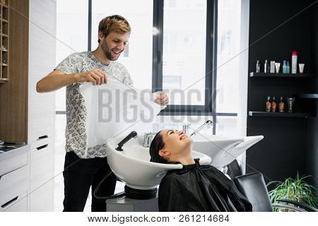 Charming young woman smiling happily while professional male hairstylist preparing her hair for the haircut drying it with a towel stock photo