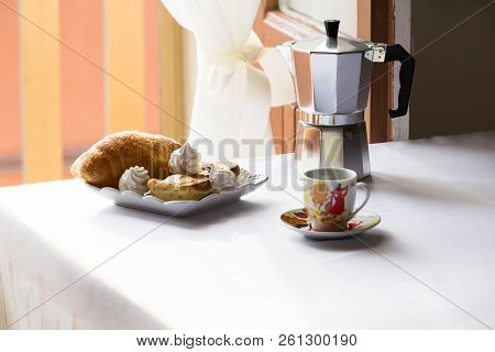 Homemade sweet breakfast of coffee and meringue and pasticiotto leccese, a table near a window stock photo