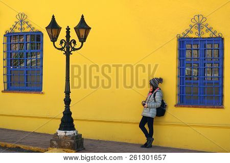 Female leaning against vivid yellow rough wall with vivid blue artistic windows and a vintage gorgeous street lamp stock photo