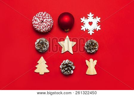 Christmas composition. New Year's wooden toys, fir cones, red ball, snowflake, gift twine on red background Flat lay top view copy space. Christmas winter decoration Nature New Year concept stock photo