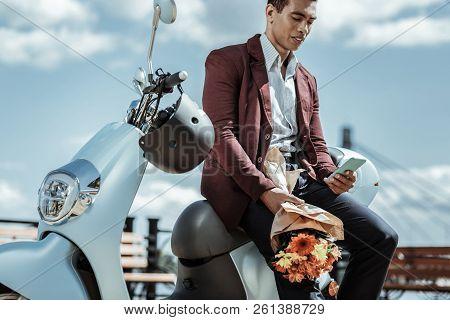 Earnest calm guy awaiting girl on motorbike stock photo